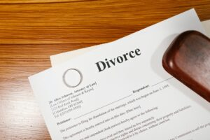 """A Document Titled """"Divorce"""" Placed on a Wooden Tabletop with a Wedding Band Placed Upon it"""
